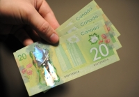 A man displays Canadian 20-dollar bills in Washington on January 14, 2013.     AFP PHOTO/Nicholas KAMM / AFP PHOTO / NICHOLAS KAMM